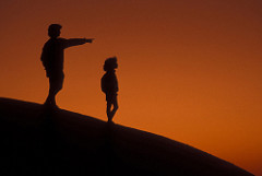 Silhouette of Mother pointing into distance with her daughter